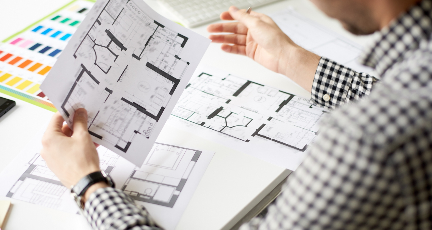 Close-up shot of confident interior designer studying floor plan while thinking over new project, office desk with color swatches and documents on background